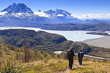 Hikers descend a grassy slope with lake, mountain and iceberg view; near Ferrier Vista Point, Torres del Paine, Patagonia, Chile, South America