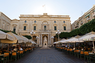 Monument to Queen Victoria and an outdoor cafe in Republic Square, in front of the National Library, Valletta, Malta, Europe