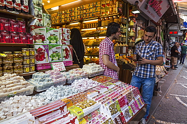 Sweet shop, man looks in wallet, busy street linking Grand and Spice Bazaarrs, Bazaar District, Istanbul, Turkey, Europe