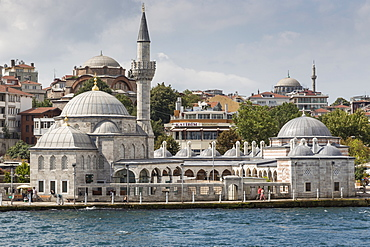 Couple walking past the Semsi Pasa Mosque, seen from the Bosphorus Strait, Uskudar, Istanbul, Turkey, Europe