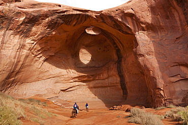 Horse riding trip, tourist with Navajo guide pass under rock arch, Monument Valley Navajo Tribal Park, Utah Arizona, United States of America, North America