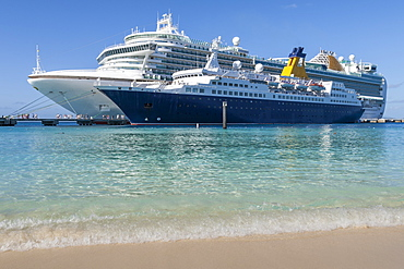 Cruise ships and disembarking passengers, seen from a white sand beach, cruise terminal; Grand Turk, Turks and Caicos, West Indies, Caribbean, Central America