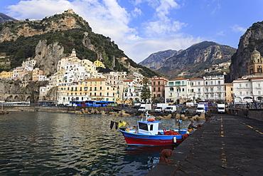 Fisherman in fishing boat and Amalfi town, Costiera Amalfitana (Amalfi Coast), UNESCO World Heritage Site, Campania, Italy, Europe