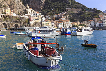 Fisherman in fishing boat in Amalfi harbour, from quayside with view towards Amalfi town, Costiera Amalfitana (Amalfi Coast), UNESCO World Heritage Site, Campania, Italy, Europe