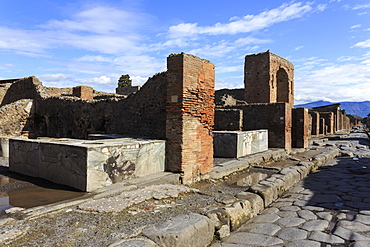 Cobbled street with thermopolium counters and arch, Roman ruins of Pompeii, UNESCO World Heritage Site, Campania, Italy, Europe