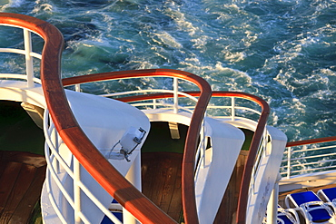 Sweeping tiers of wooden handrails at the stern of a cruise ship, lit by late evening sun, North Sea, off Norway, Scandinavia, Europe