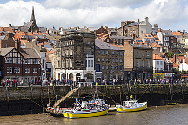 Boats moored on the West Side of the River Esk, with many passers-by on Pier Road, Whitby, North Yorkshire, Yorkshire, England, United Kingdom, Europe