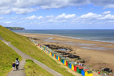 Elevated view of colourful beach huts on West Cliff Beach, mother and daughter hand in hand, Whitby, North Yorkshire, England, United Kingdom, Europe