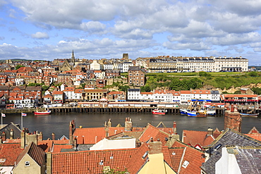 View across rooftops to West Side town, boats, pier, fish market and elegant hotels, Whitby, North Yorkshire, England, United Kingdom, Europe