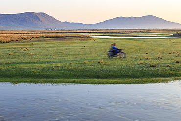 Nomads on motorcycle pass in a blur, river and distant gers, dawn, Nomad camp, Gurvanbulag, Bulgan, Northern Mongolia, Central Asia, Asia