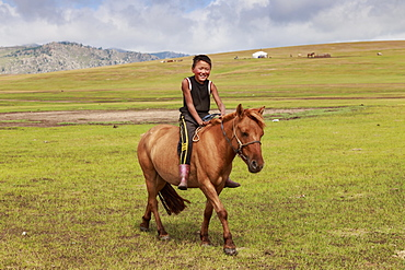 Horse and smiling boy riding bareback with ger and hills behind at summer nomad camp, Khujirt, Uvurkhangai (Ovorkhangai), Central Mongolia, Central Asia, Asia