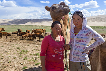 Nomadic camel herders, mother and daughter, with two hump Bactrian camel with Khongoryn Els sand dunes behind, Gobi Desert, Mongolia, Central Asia, Asia