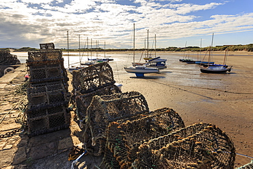 Lobster pots on harbour wall and yachts on beach at low tide on a summer evening, Beadnell, Northumberland, England, United Kingdom, Europe