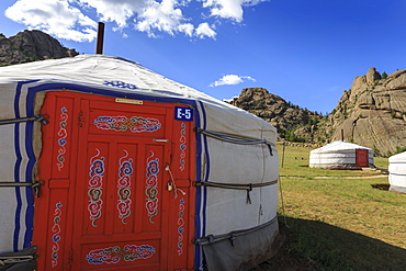 Tourist ger camp in front of rocky outcrop in fine weather in summer, Terelj National Park, Central Mongolia, Mongolia, Central Asia, Asia