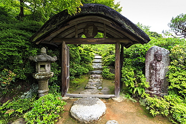 Okochi Sanso Villa, cobbled path through a wooden gateway in the verdant stroll garden in summer, Arashiyama, Kyoto, Japan, Asia