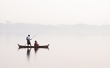 Man punting small wooden boat with bamboo pole and woman with baby at sunrise crossing Taungthaman Lake, Amarapura, Myanmar (Burma), Asia