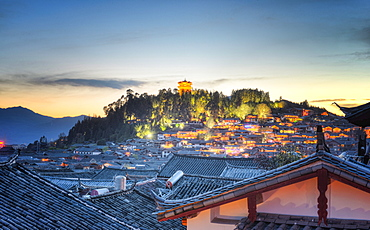 Night falls over Lijiang and Shizishan (Lion Hill with WanGu Tower) while the city lights slowly come to life, Lijiang, Yunnan, China, Asia