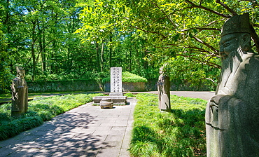 Stone statues watching over an old tomb in the gardens of Hangzhou, Zhejiang, China, Asia