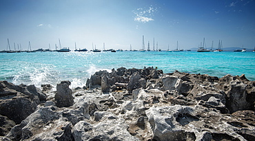 Jagged rocks with sailboats idling in the azure waters of Formentera, Balearic Islands, Spain, Mediterranean, Europe
