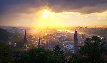 Golden afternoon sun dramatically breaking through rain clouds over the spires of Heidelberg Old Town, Baden-Wurttemberg, Germany, Europe