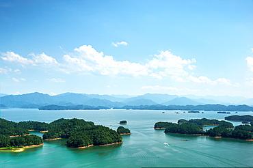 A white boat making its way across Qiandao (Thousand Islands) Lake, Chunan, Zhejiang, China, Asia - 1171-255