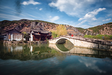 Guan Yin Gorge Park in a long exposure, with an actor in Monkey King costume sitting on the bridge, waiting for visitors, Lijiang, Yunnan, China, Asia