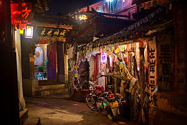 Alley at night with Tibetan style hostel and motorcycle in Lijiang Old Town, UNESCO World Heritage Site, Lijiang, Yunnan, China, Asia