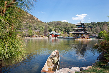 Scene at Black Dragon Pool (Heilongtan) with boat carrying wicker baskets and Moon Embracing Pavilion, Lijiang, Yunnan, China, Asia .