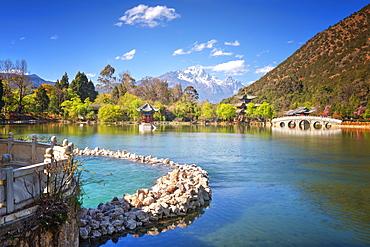 Heilongtan (Black Dragon Pool) with pool, pagodas, white marble bridge and mountain backdrop, Lijiang, Yunnan, China, Asia