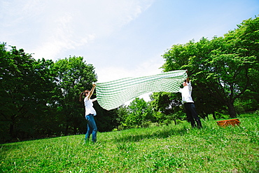 Couple Spreading Picnic Cloth in Park