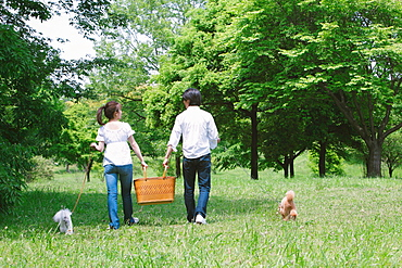Couple Walking with Pets in Park
