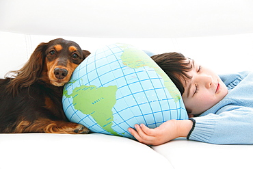 Boy and dog lying down on the couch