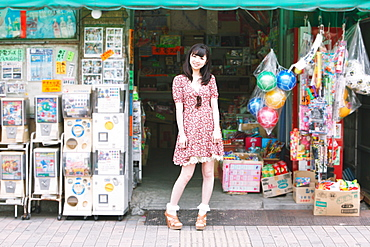 Japanese girl standing in front of an old candy shop