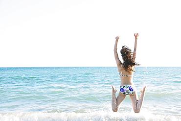 Japanese woman in a bikini jumping by the sea