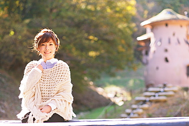Portrait of a Japanese woman in a white cardigan looking at camera
