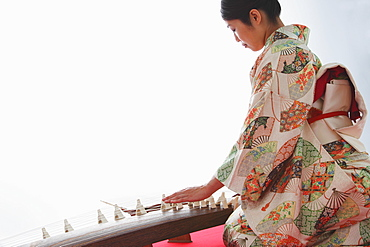 Japanese woman in a kimono playing the koto