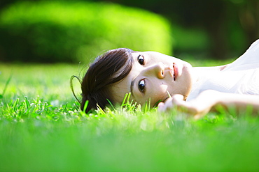 Young Woman Lying on Grass In Park