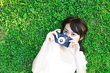 Young Woman Lying on Grass Holding Camera