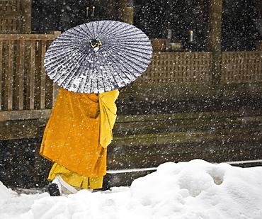 A Bhuddist monk walks through a snow flurry in Koyasan, a centre for Shingon Esoteric Buddhism, Koyasan, Osaka, Japan