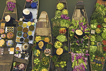 Aerial view of a floating market on a canal in Bangkok, local boats laden with fresh food, moored close together, Bangkok, Thailand,