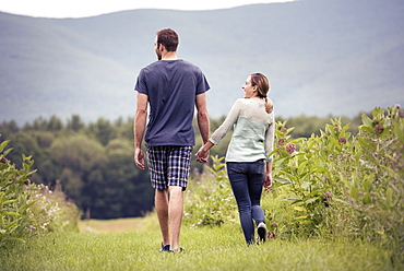 A couple, man and woman walking through a meadow holding hands.