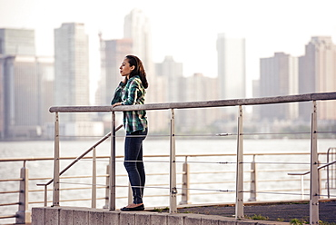 A woman standing on the waterfront, view to the city over the water in New York City.