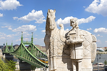 A statue of St Stephen in front of the Cave Church with a view of the Chain Bridge, Budapest, Hungary