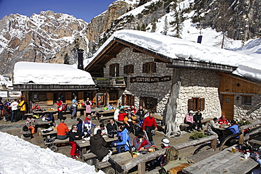 Guests sitting on terrace of the hut Scotoni in sunshine, South Tyrol, Italy
