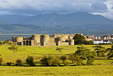 View of Beaumaris castle at Island of Anglesey with mountain ranges in background, Wales