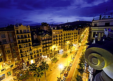 View of buildings and street lights at evening in Gracia, Barcelona, Spain