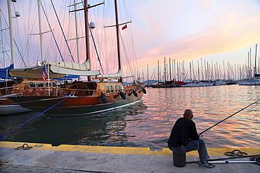 Man fishing at harbor at sunset in Bodrum Peninsula, Turkey