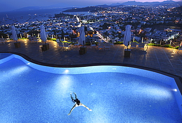 View of person swimming in pool of Hotel The Marmara Pool and cityscape in Bodrum, Turkey