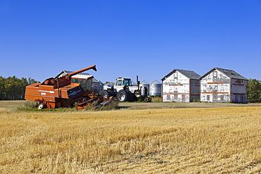 View of harvester in landscape with garnary on Highway 6, Saskatchewan, Canada