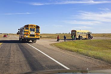 Children at school bus on Highway 15, Saskatchewan, Canada